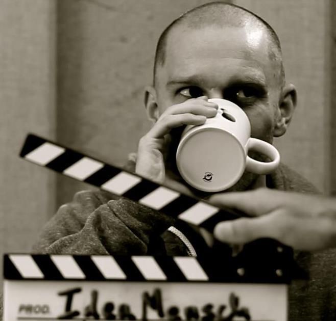 CMO drinking a cup of coffee behind a scene sign.