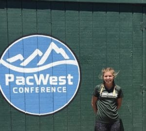 standing next to PacWest banner after the conference meet
